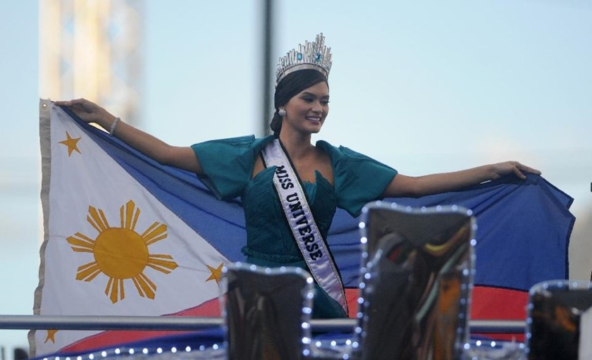 Miss Universe Pia Alonzo Wurtzbach waves a Philippine flag during her victory homecoming parade in Manila on January 25, 2016