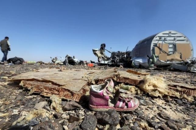 A child's shoe is seen in front of debris from a Russian airliner which crashed at the Hassana area in Arish city, north Egypt, November 1, 2015.