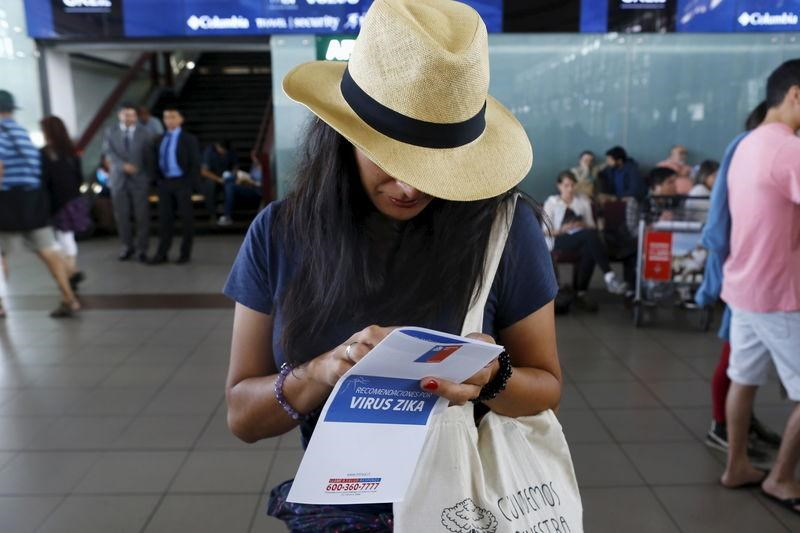 A woman holds a zika virus flyer from an information campaign by the Chilean Health Ministry at the departures area of Santiago's international airport, Chile January 28, 2016. The flyer reads: 'Zika virus recommendations.'