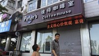 A boy looks up as he walks past the closed coffee shop owned by Canadian couple Kevin Garratt and Julia Dawn Garratt in Dandong, Liaoning province, August 5, 2014.
