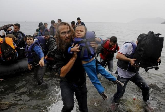 File photograph shows a volunteer carrying a Syrian refugee child off an overcrowded dinghy at a beach after the migrants crossed part of the Aegean Sea from Turkey to the Greek island of Lesbos September 23, 2015.