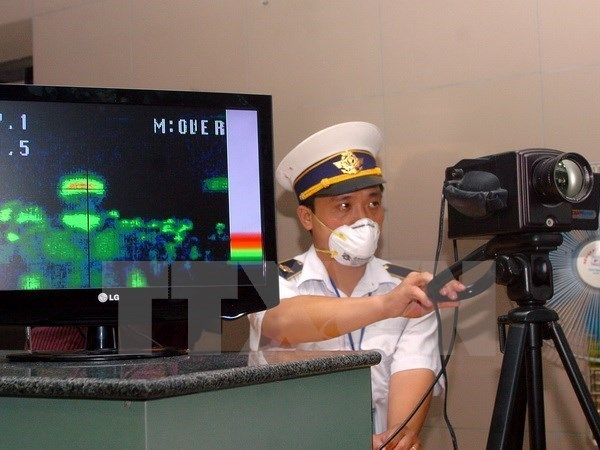 A customs officer conducts temperature screening at Noi Bai International Airport in Hanoi, Vietnam. Photo: VNA