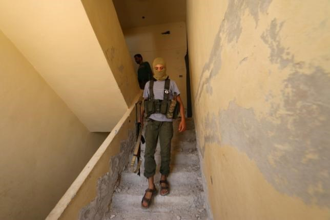 A Nusra Front fighter walks with his weapon inside a building in the Sheikh Maksoud neighbourhood of Aleppo, Syria August 3, 2015.