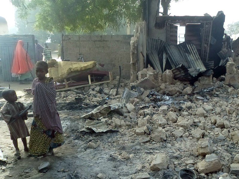 Children stand near the rubble of a burnt house after Boko Haram attacks at Dalori, in northeastern Nigeria, on Sunday. Photo: AFP
