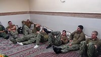 An undated picture released by Iran's Revolutionary Guards website shows American sailors sitting in a unknown place in Iran.
