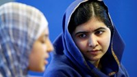 Malala Yousefzai (R) listens to 17 year old Syrian refugee Muzoon Almellehan speak to journalists at the City Library in Newcastle Upon Tyne, Britain December 22, 2015.
