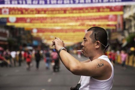 A Chinese tourist with a tattoo of China's late Chairman Mao Zedong takes pictures in Bangkok's Chinatown decorated for the Chinese Lunar New Year.
