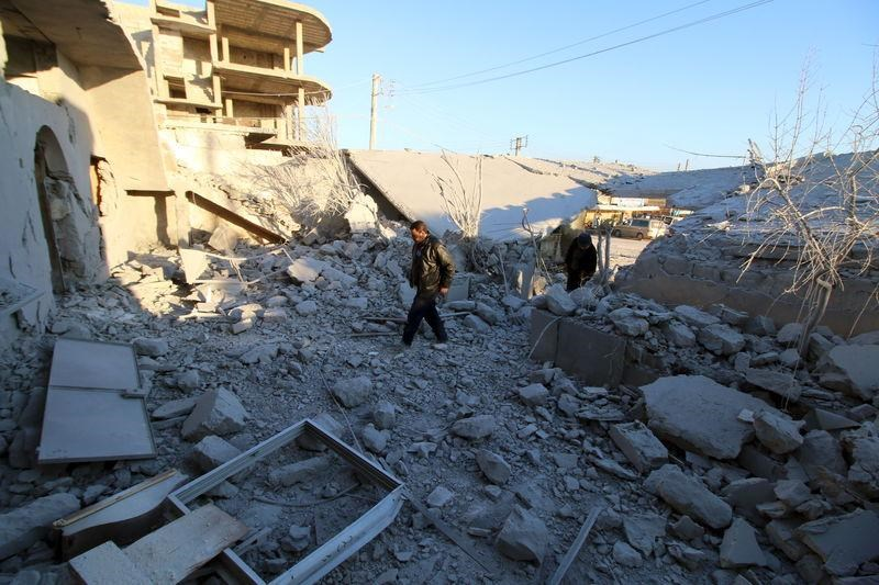 Residents inspect damage after airstrikes by pro-Syrian government forces in Anadan city, about 10 kilometers away from the towns of Nubul and Zahraa, Northern Aleppo countryside, Syria February 3, 2016.