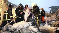 Rescue personnel help a victim at a damaged building after an earthquake in Tainan, southern Taiwan, February 6, 2016
