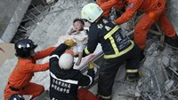 Rescue personnel help a child rescued at the site where a 17-storey apartment building collapsed during an earthquake in Tainan, southern Taiwan, February 6, 2016.