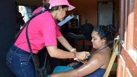 A health worker sprays mosquito repellent on a pregnant woman's arm, during a campaign to fight the spread of Zika virus in Soledad municipality near Barranquilla, Colombia, in this February 1, 2016 handout photo supplied by the Soledad Municipality.