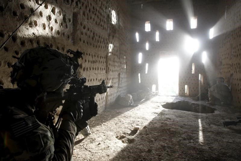U.S. soldier Nicholas Dickhut from 5-20 infantry Regiment attached to 82nd Airborne points his rifle at a doorway after coming under fire by the Taliban while on patrol in Zharay district in Kandahar province, southern Afghanistan in this April 26, 2012 file photo.