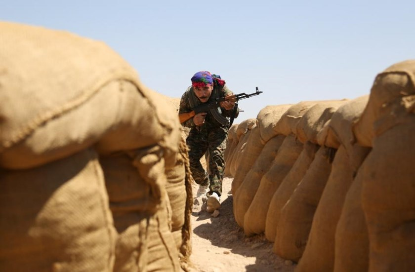 A fighter from the Kurdish People Protection Unit (YPG) walks between sandbags on the front line in the northeastern Syrian city of Hasakeh on September 4, 2015
