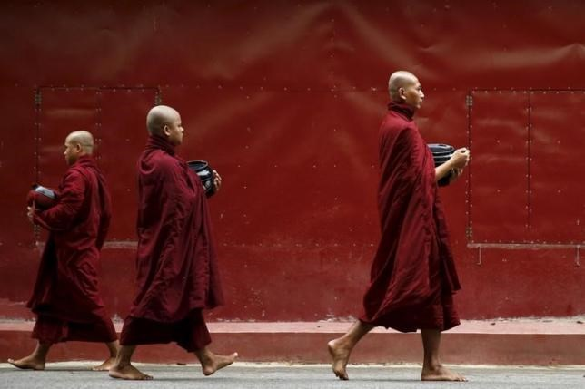 Buddhist monks walk inside the Masoyein monastery complex in Mandalay October 7, 2015.