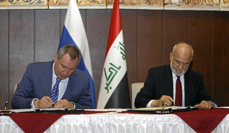 Iraqi Foreign Minister Ibrahim al-Jaafari (R) and Russia's Deputy Prime Minister Dmitry Rogozin (L) sign documents in Baghdad, Iraq February 11, 2016.
