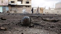 An unexploded cluster bomblet is seen along a street after airstrikes by pro-Syrian government forces in the rebel held al-Ghariyah al-Gharbiyah town, in Deraa province, Syria February 11, 2016.