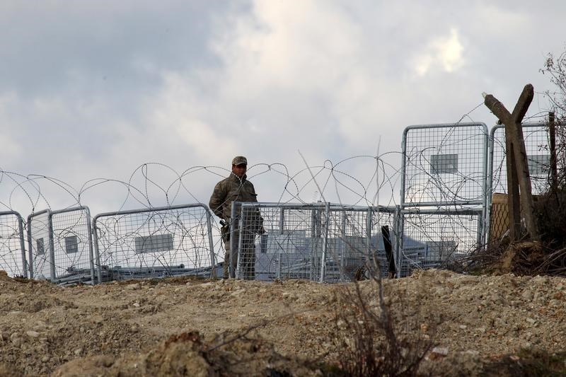A Turkish soldier standing guard is seen from the Syrian town of Khirbet Al-Joz at the Turkish-Syrian border, in Latakia countryside, where internally displaced Syrian people are waiting to get permission to cross into Turkey, February 7, 2016.
