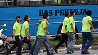 Factory workers walk along a road after disembarking from a bus in Penang, Malaysia