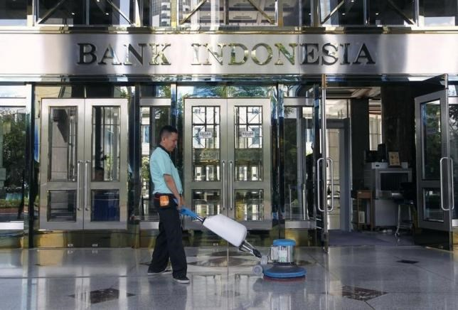 A worker cleans near the front entrance of the Bank Indonesia's headquarters in Jakarta, Indonesia January 14, 2016.