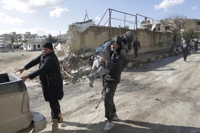 A man carries an injured woman in a site hit by what activists said were airstrikes carried out by the Russian air force in the rebel-controlled area of Maaret al-Numan town in Idlib province, Syria, January 9, 2016.