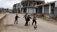 Children play near damaged buildings in the rebel held historic southern town of Bosra al-Sham, Deraa, Syria February 23, 2016.
