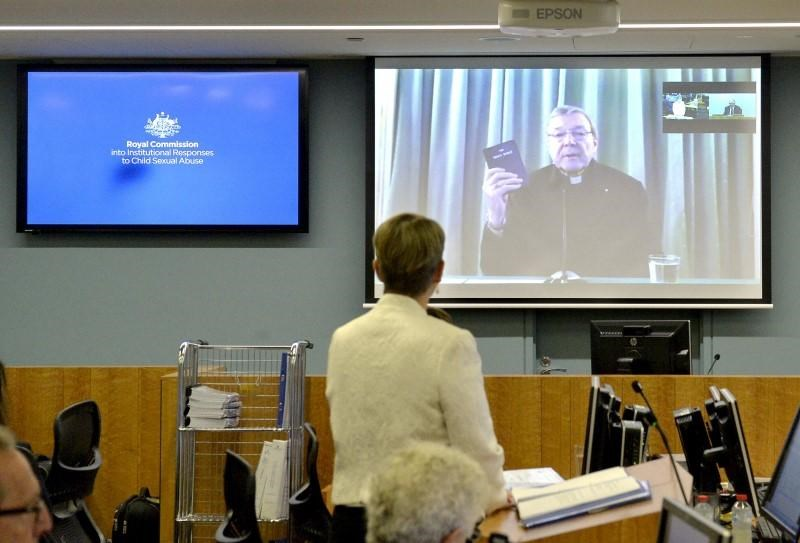 Senior Counsel Assisting Gail Furness stands in front of a screen displaying Australian Cardinal George Pell as he holds a bible