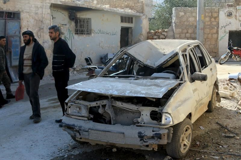 Residents stand near a damaged car in the town of Darat Izza, province of Aleppo, Syria February 28, 2016.