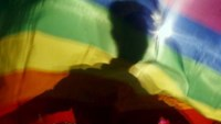 A gay man is silhoutted on a gay rainbow flag during a demonstration for gay rights in Hanoi.