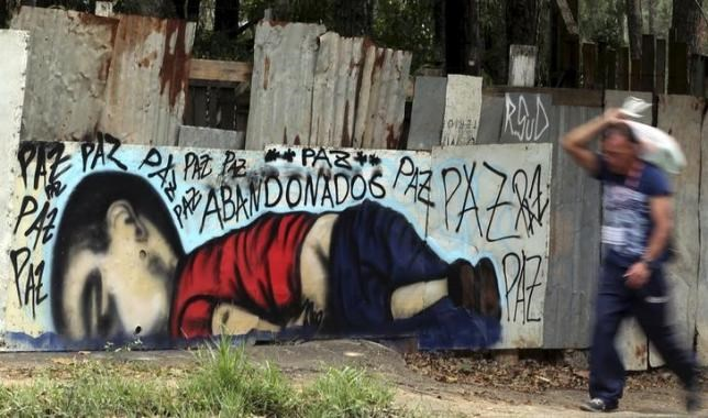 A person walks past a graffiti depicting the drowned Syrian toddler Aylan Kurdi in Sorocaba, Brazil, September 5, 2015.
