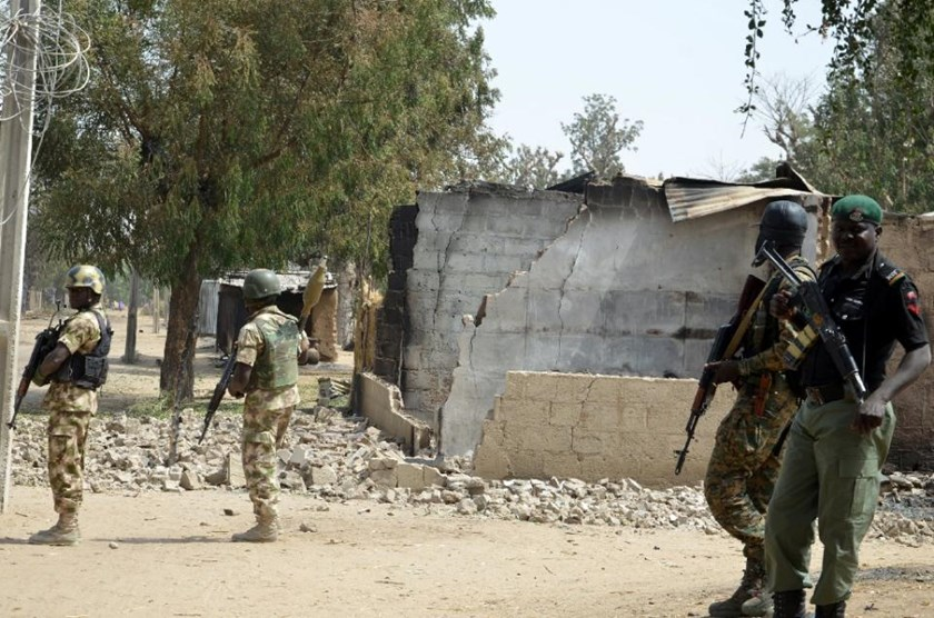 Soldiers and policemen walk past burnt house on February 4, 2016 during a visit to the village of Dalori village, northeastern Nigeria, after an attack by Boko Haram insurgents on the village left at least 85 people dead on January 30, 2016