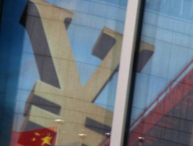 China's national flag is reflected on an advertisement of a commercial bank bearing the sign of Chinese Yuan at a branch of a commercial bank at a business district in Beijing, China, January 21, 2016.