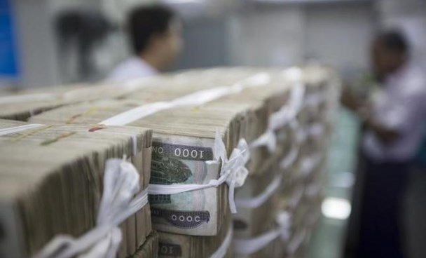 Stacks of Myanmar kyat are seen on the counter before a client collects them, at a bank in Yangon, Myanmar October 19, 2015.