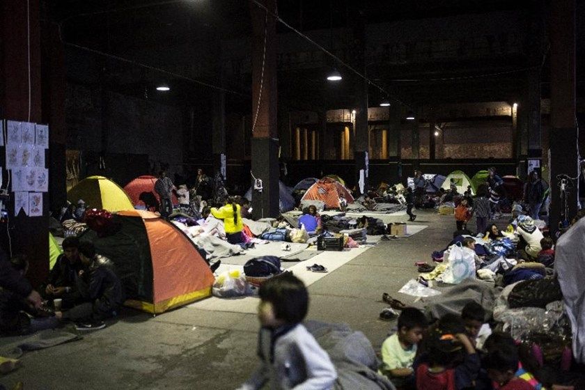 People from Afghanistan go about their daily lives in a migrant and refugee makeshift camp at Piraeus harbour in Athens