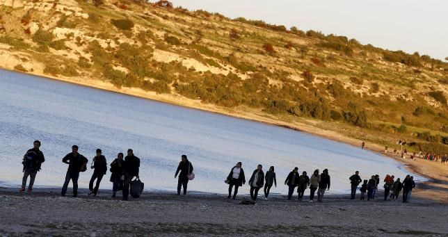 Refugees walk along a beach before trying to travel to the Greek island of Chios from the western Turkish coastal town of Cesme, in Izmir province, Turkey, March 5, 2016.