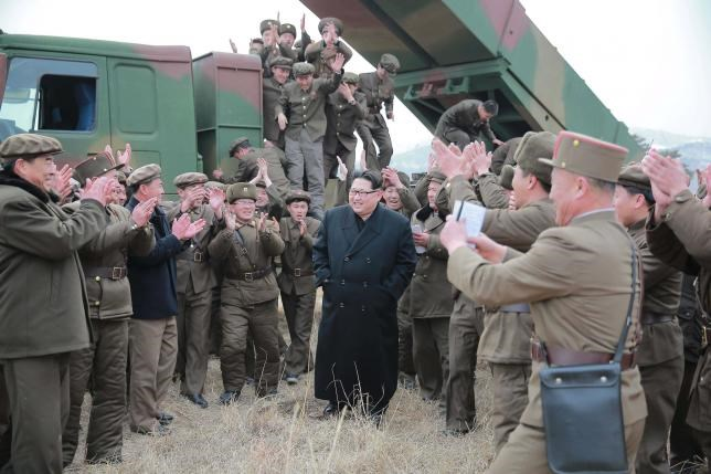 North Korean leader Kim Jong Un (C) smiles as he guides a test fire of a new multiple launch rocket system in this undated photo released by North Korea's Korean Central News Agency (KCNA) in Pyongyang March 4, 2016.