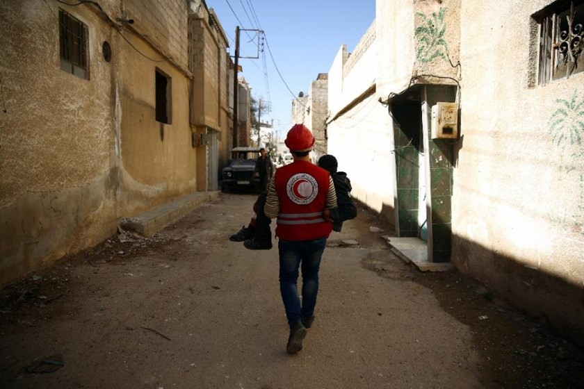 A member of the Syrian Arab Red Crescent carries a wounded boy following an airstrike in the rebel-held city of Douma in Eastern Ghouta, on February 26, 2016