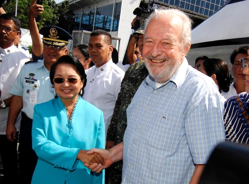 Then Philippine President Gloria Macapagal Arroyo (L) shakes hands with freed Irish priest Michael Sinnott at the Villamor Airbase in Manila, in 2009