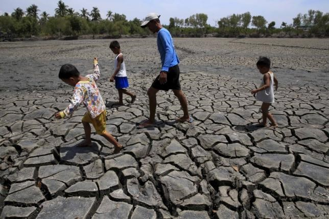 A father with his children walk over the cracked soil of a 1.5 hectare dried up fishery at the Novaleta town in Cavite province, south of Manila May 26, 2015.