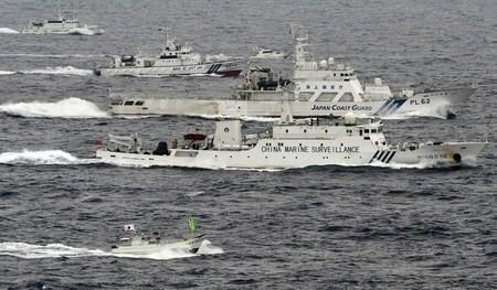 An aerial photo shows a Chinese marine surveillance ship Haijian No. 66 cruising next to Japan Coast Guard patrol ships in the East China Sea
