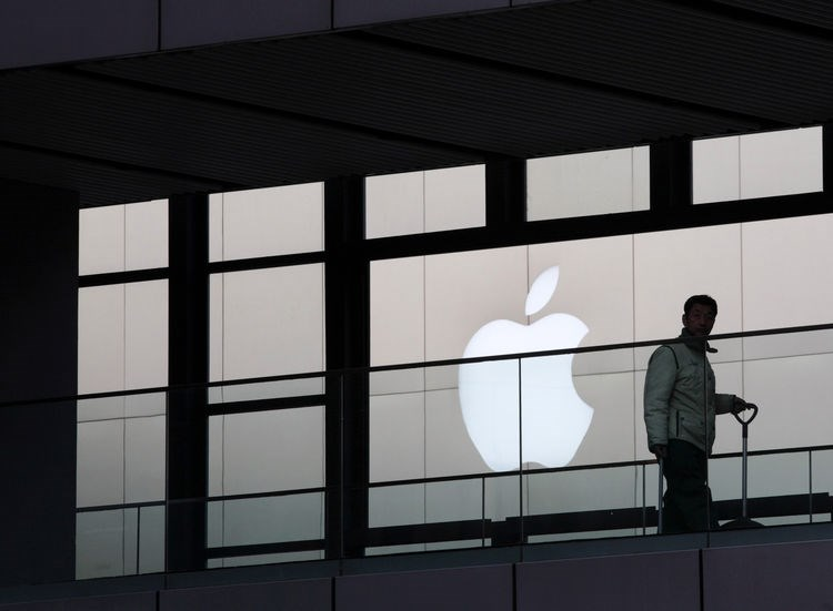 A worker walks past the Apple Inc. logo in the Sanlitun area of Beijing, China.