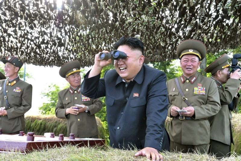 North Korean leader Kim Jong Un looks through a pair of binoculars during an inspection of the Hwa Islet Defence Detachment standing guard over a forward post off the east coast of the Korean peninsula