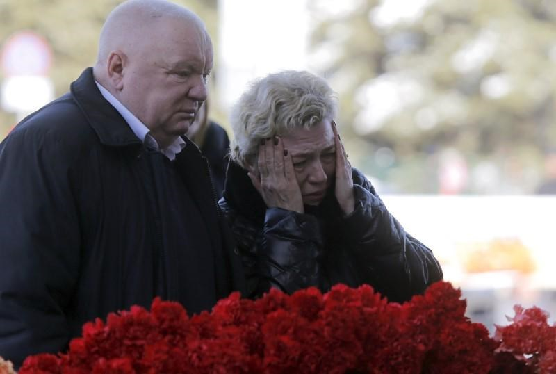 People react while standing near flowers left in memory of the victims of the crashed Boeing 737-800 Flight FZ981 operated by Dubai-based budget carrier Flydubai, outside the airport of Rostov-On-Don, Russia, March 20, 2016.