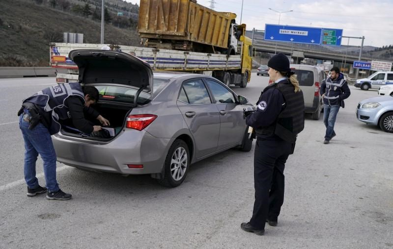 A police officer searches a car during a security control check in Ankara, Turkey March 17, 2016.