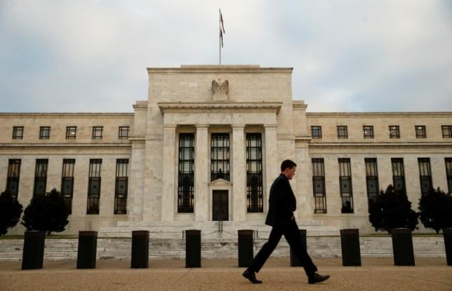 A man walks past the Federal Reserve in Washington, December 16, 2015.