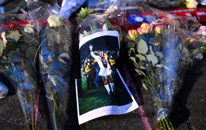 A man lays flowers near the statue of Johan Cruyff in front the Olympic Stadium on March 24, 2016 in Amsterdam