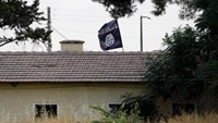 An Islamic State flag flies over the custom office of Syria's Jarablus border gate as it is pictured from the Turkish town of Karkamis, in Gaziantep province, Turkey August 1, 2015.