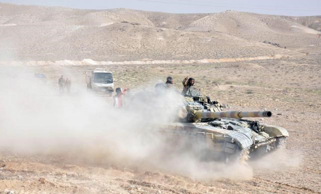 Forces loyal to Syria's President Bashar al-Assad drive a tank during their offensive to recapture the historic city of Palmyra in this picture provided by SANA on March 24, 2016.