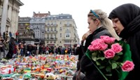 People observe a minute of silence at a street memorial to victims of Tuesdays's bombings in Brussels, Belgium, March 24, 2016.