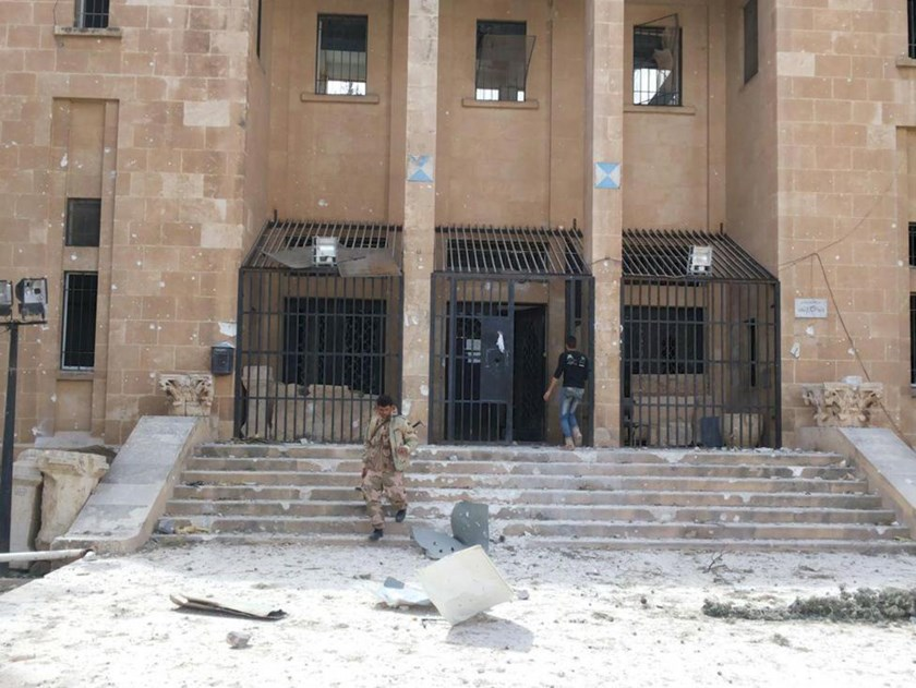 A member of forces loyal to Syria's President Bashar al-Assad walks down the stairs of the museum of the historic city of Palmyra, after government forces recaptured the city, in Homs Governorate in this handout picture provided by SANA on March 27, 2016.