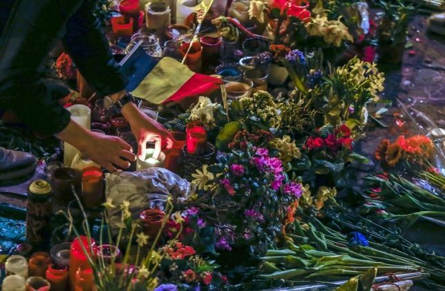 A woman lights a candle at a street memorial for the victims of bomb attacks in Brussels metro and Brussels international airport of Zaventem, in Brussels, Belgium, March 28, 2016.